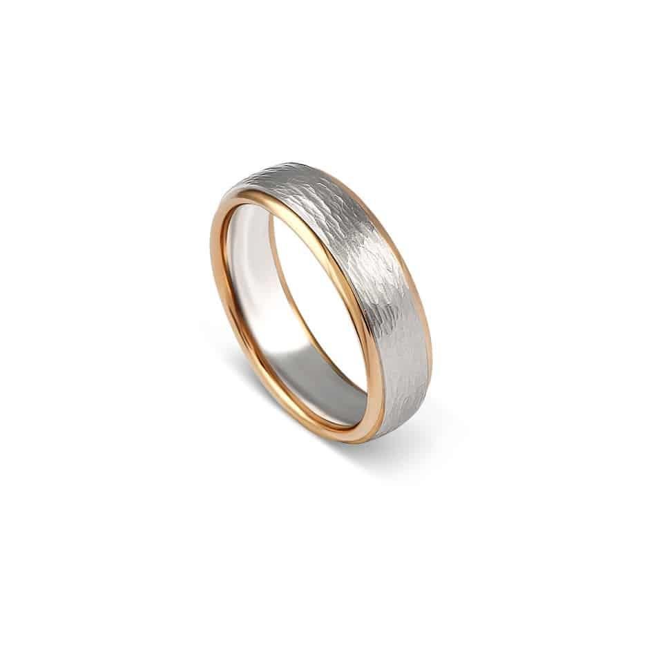 "Christian Bauer wedding bands are beautifully engineered.  Here's a distinctive men's band from the German label, blending an organic rippled texture with polished bands of rose gold.  The workmanship is extraordinary; we have stocked Christian Bauer wedding bands for many years and continue to be impressed with their innovative approach.  You'll be pleased with the fit and comfort of this wedding ring, particularly when you start receiving compliments on your choice… *Christian Bauer wedding bands are ordered to size, so please open Live Chat to enquire about prices and availability.Authorised Christian Bauer London StockistMen's platinum wedding ringRing number 274461Metal: Platinum, 750 Rose GoldWidth: 6.5 mm""Contact us / chat with us to explore our exquisite collection of Wedding Platinum Rings Christian Bauer men's textured wedding bandA textured wedding band is an interesting and unusual choice that really makes a statement.  Christian Bauer crafts a range of textures on its wedding bands, from sandblasted circles to precision-cut edges and wavy, organic rings.  The brand is also known for using coloured golds in a unique way.  This ring contrasts both texture and colour, and is perfect for wearing all by itself.   If it's the only jewellery you're likely to wear then this wedding band is striking enough to take all the attention."