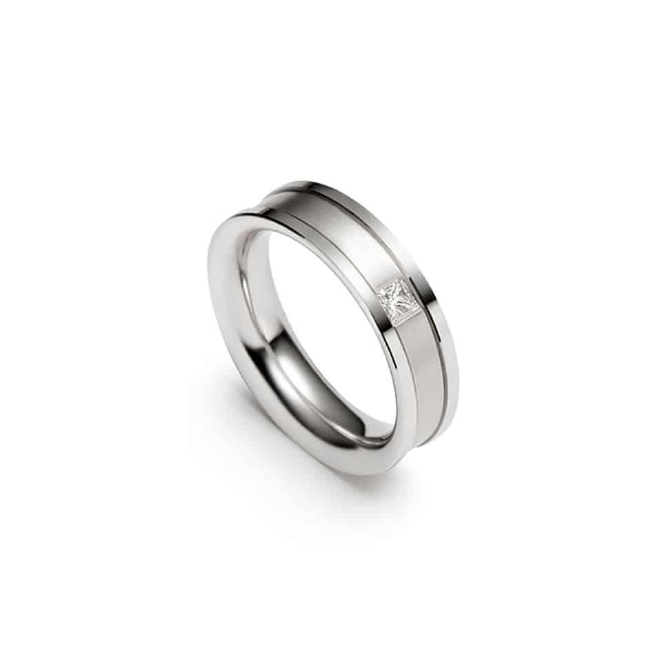 Christian Bauer Princess Cut Wedding RingJust a little more than a plain wedding band… The designers at Christian Bauer added a channel with a square diamond for extra interest in this classic-looking new wedding band. It is beautifully made in white gold and stamped with the Christian Bauer fir tree (to show authenticity). With the subtle addition of a Princess-cut diamond, this unisex wedding band coordinates with your engagement diamond or can be elegantly worn alone. It is contemporary, timeless, and ready to last all of your life. *Your Christian Bauer wedding band is ordered to size, unless we have your size in stock. Please open Live Chat to enquire or order.*Authorised Christian Bauer UK Stockist in LondonChristian Bauer wedding band – 241433Metal: 18ct White GoldDiamond cut: PrincessStone setting style: Rub-over settingDiamond weight: 0.09ct white diamondsDiamond quality: White diamonds, G-H Colour and VS ClarityFinger size pictured: SWidth: 5.5mmMaking your Christian Bauer wedding bandThe jewellers at Christian Bauer still incorporate many traditional skills into their work. But the production facility is a thoroughly modern eco-building, with its own water treatment works, and the latest state-of-the-art machinery. The jewellers blend handiwork and technology to bring your Christian Bauer wedding ring to life.Diamonds are selected from the top end of the quality scale and painstakingly hand-set for a flawless finish. Christian Bauer wedding rings are mostly made from platinum, the strongest precious metal, with highlights of white gold, yellow gold, and rose gold. Interestingly, the company will only use previously-mined metal – pledging to disturb no earth to create your wedding ring.